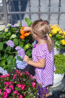 Weinig aardig meisje die bloemen met wateringcan water geven