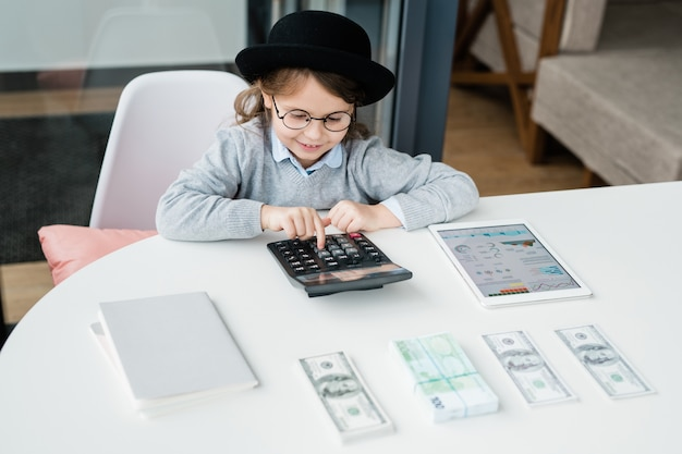 Weinig accountant die calculator gebruikt terwijl hij salaris of geld telt en financiële analyse maakt per bureau