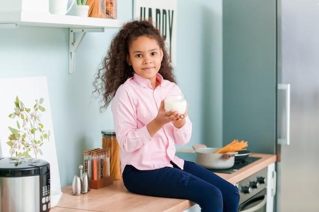 Weinig afrikaans-amerikaans meisje met melk in keuken