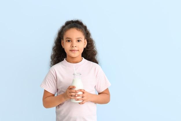 Weinig afrikaans-amerikaans meisje met melk op kleur Premium Foto