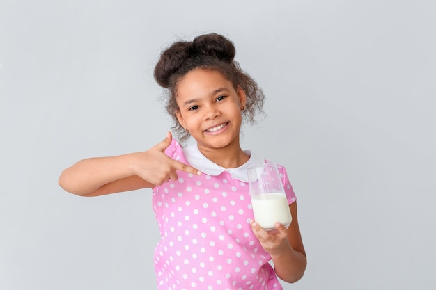 Weinig afrikaans-amerikaans meisje met melk op licht
