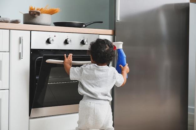 Weinig afrikaans-amerikaanse baby die met wasmiddel en oven thuis speelt. kind in gevaar