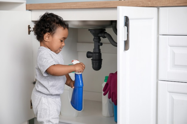 Weinig afrikaans-amerikaanse baby die met wasmiddelen thuis speelt. kind in gevaar