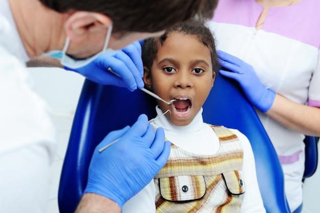 Weinig afrikaans meisje met donkere huid in tandheelkunde