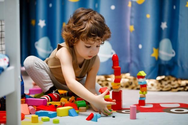 Weinig autistische jongen die met kubussen thuis speelt