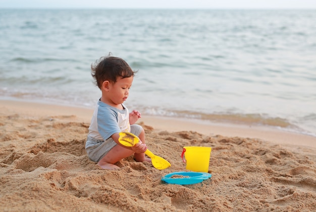 Weinig aziatisch babyjongen het spelen zand bij alleen strand.
