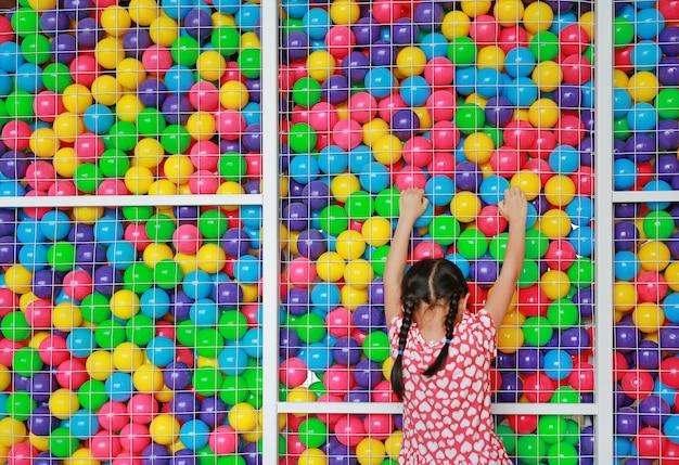 Weinig aziatisch jong geitjemeisje die beklimmen op kooi van speelplaats kleurrijke stuk speelgoed bal spelen.