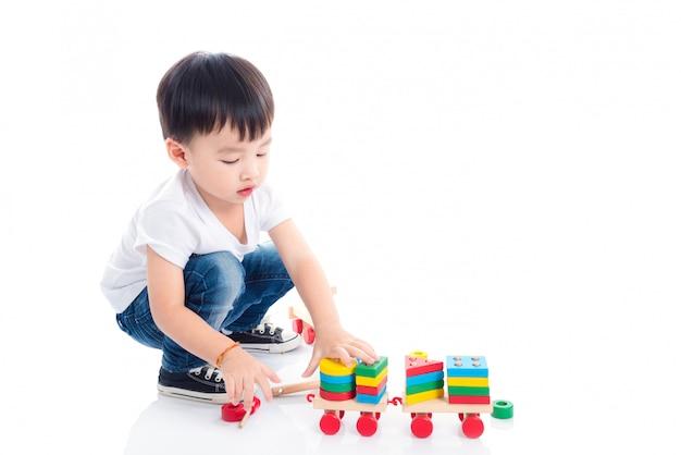 Weinig aziatisch jongens speelstuk op de vloer over witte achtergrond
