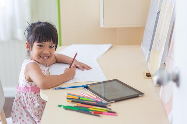 Weinig aziatisch kind die een potlood gebruiken om op notitieboekje bij het bureau te schrijven