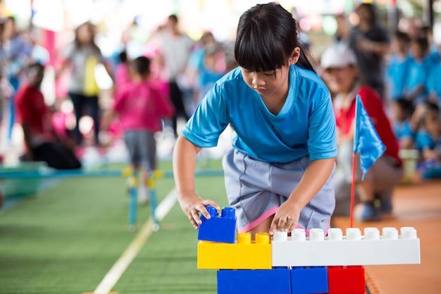 Weinig aziatisch kind die met kleurrijke bouwblokken spelen