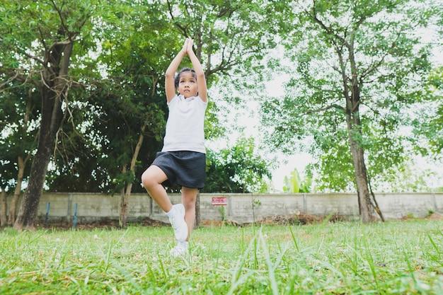 Weinig aziatisch kindmeisje dat yoga in het openbare park doet.