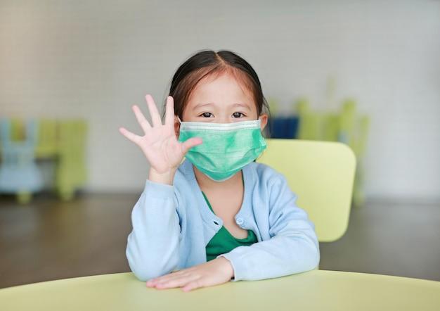 Weinig aziatisch kindmeisje die een beschermend masker met het tonen van vijf vingers dragen