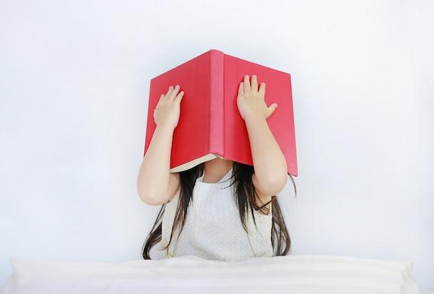Weinig aziatisch kindmeisje die gezicht met open hardcover boekzitting op bed met hoofdkussen verbergen.