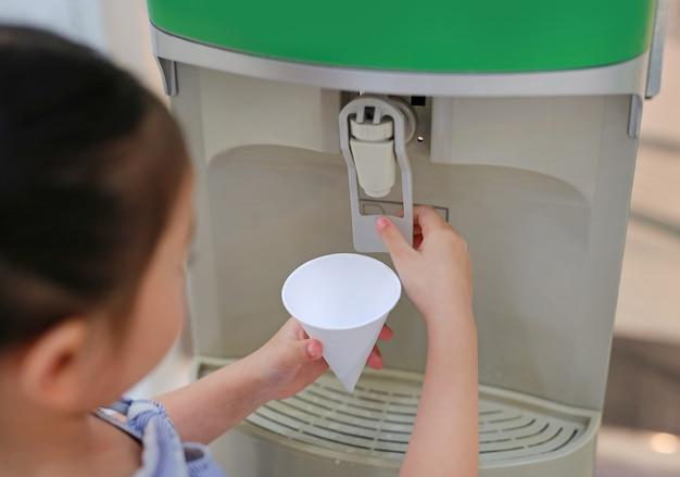 Weinig aziatisch kindmeisje drukt het drinkwater