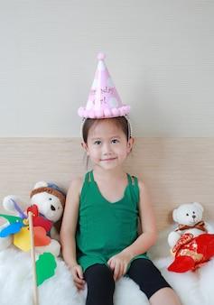 Weinig aziatisch kindmeisje met de gelukkige zitting van de verjaardagshoed op het bed.