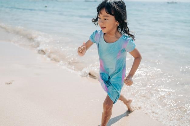 Weinig aziatisch meisje dat de golven loopt te vermijden