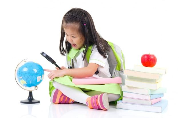 Weinig aziatisch meisje dat door vergrootglas bol bekijkt, die op witte achtergrond wordt geïsoleerd.