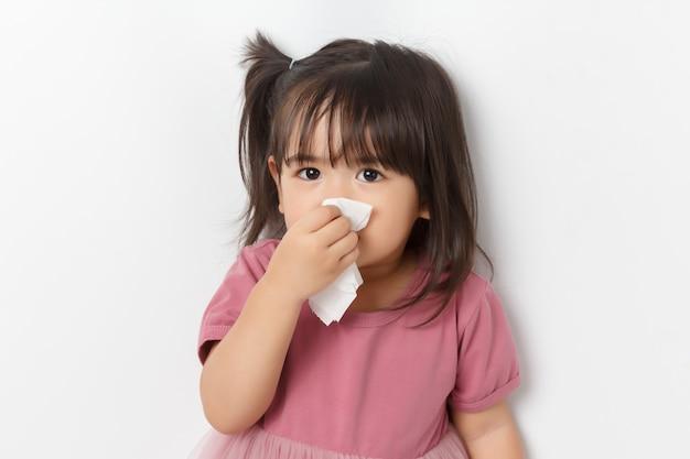 Weinig aziatisch meisje dat een weefsel houdt en haar neus blaast. kid met koude rhinitis.