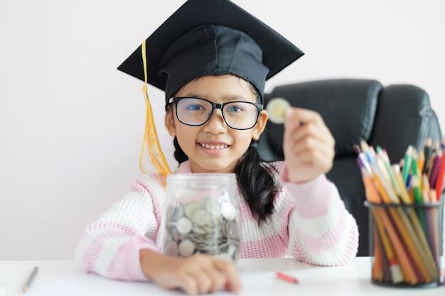 Weinig aziatisch meisje dat gediplomeerde hoed draagt die duidelijke glaskruik koestert
