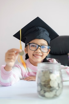 Weinig aziatisch meisje dat gediplomeerde hoed draagt die een muntstuk zet in duidelijke glaskruik