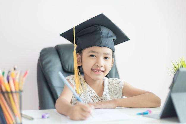Weinig aziatisch meisje dat gediplomeerde hoed draagt die huiswerk en glimlach met geluk doet