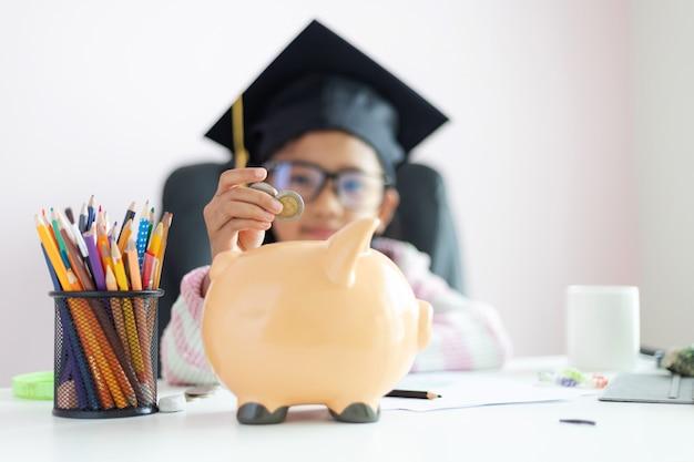 Weinig aziatisch meisje dat het muntstuk in spaarvarken zet en met geluk voor geldbesparing aan rijkdom in de toekomst van onderwijsconcept glimlacht selecteert de nadruk ondiepe diepte van gebied