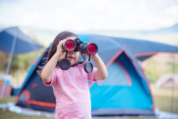 Weinig aziatisch meisje dat in binoculair kamp bekijkt