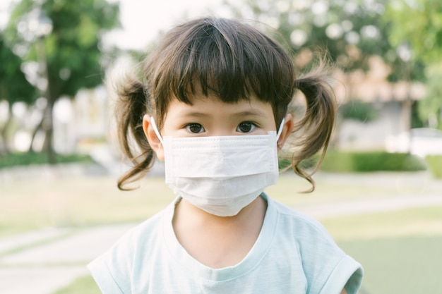 Weinig aziatisch meisje dat masker draagt voor beschermt pm2.5 en coronavirus-concept