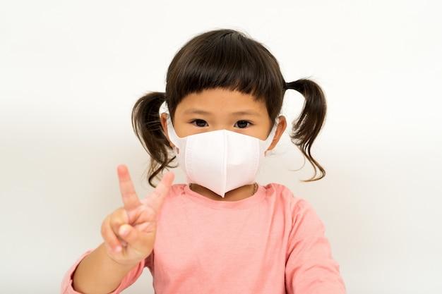 Weinig aziatisch meisje dat masker draagt voor beschermt
