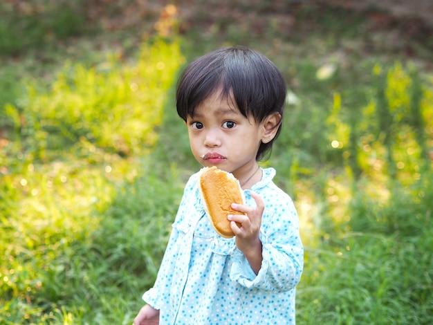 Weinig aziatisch meisje dat met vies gezicht brood op het groene de zomergebied eet