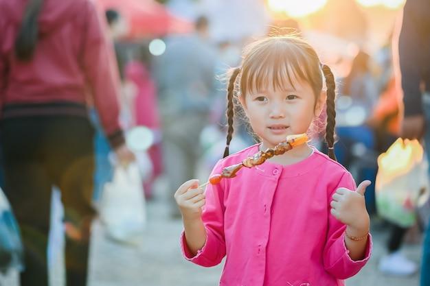 Weinig aziatisch meisje dat op straat van bangkok loopt, koopt barbecue en straatvoedsel eet in avondtijd