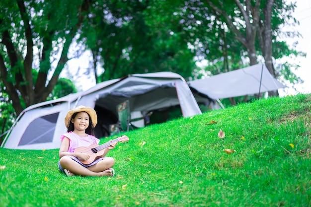 Weinig aziatisch meisje dat ukelele of hawaiiaanse gitaar in het park speelt tijdens het kamperen in de zomer