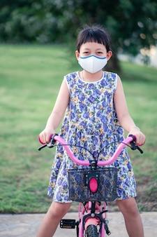 Weinig aziatisch meisje die gezichtsmasker dragen en haar fiets buiten met glimlach berijden en gelukkig