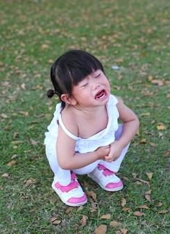 Weinig aziatisch meisje die in park schreeuwen