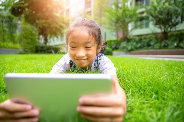 Weinig aziatisch meisje die op gras liggen en op computertablet in het park letten