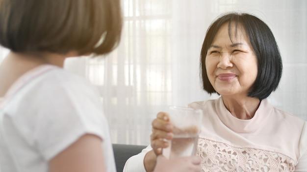 Weinig aziatisch meisje geeft een glas water aan haar grootmoeder