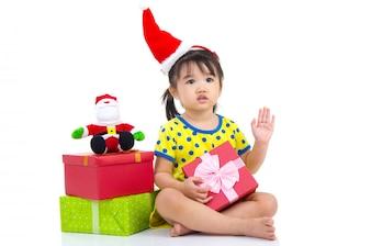 Weinig Aziatisch meisje in Kerstmanhoed en de doos van de Kerstmisgift die op wit wordt geïsoleerd