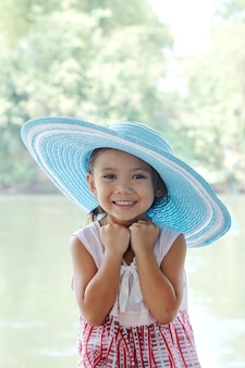Weinig aziatisch meisje in openlucht in de zomerhoed