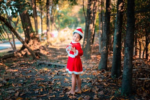 Weinig aziatisch meisje in rood santa claus-kostuum met huidige doos in het park