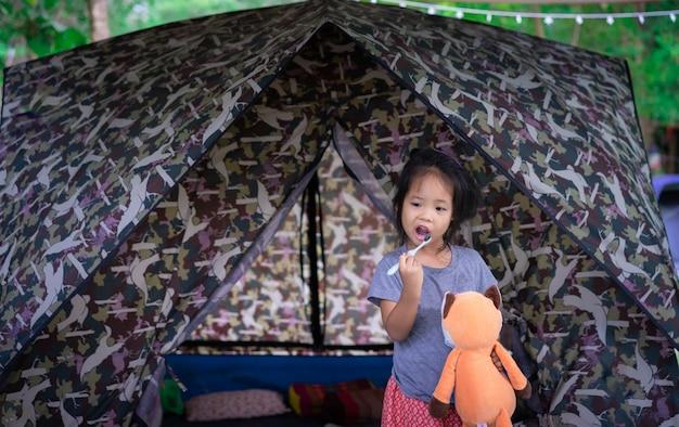 Weinig aziatisch meisje tanden poetsen in de ochtend tijdens het kamperen