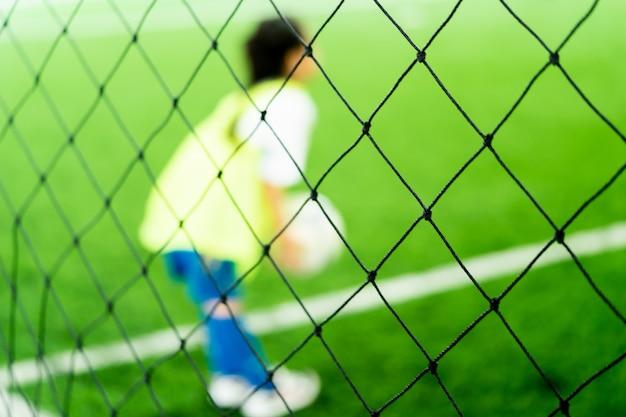 Weinig aziatisch meisje traint in overdekt voetbalveld wazig