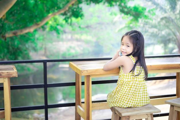 Weinig aziatisch meisje, zittend op de stoel aan houten tafel op buiten restaurant