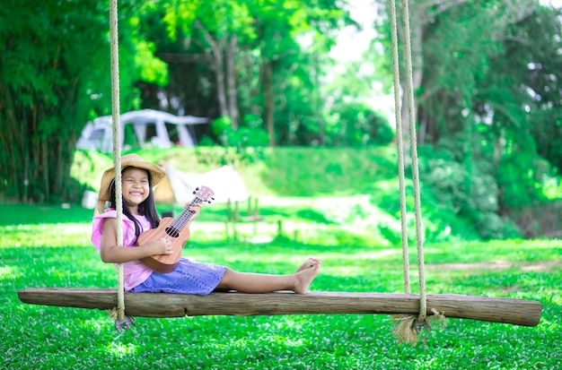Weinig aziatisch meisje zittend op houten schommel ukulele spelen tijdens het kamperen in natuurpark