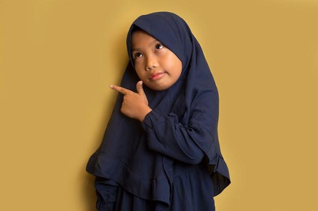 Weinig aziatisch moslim hijabmeisje met handpunt op lege ruimte