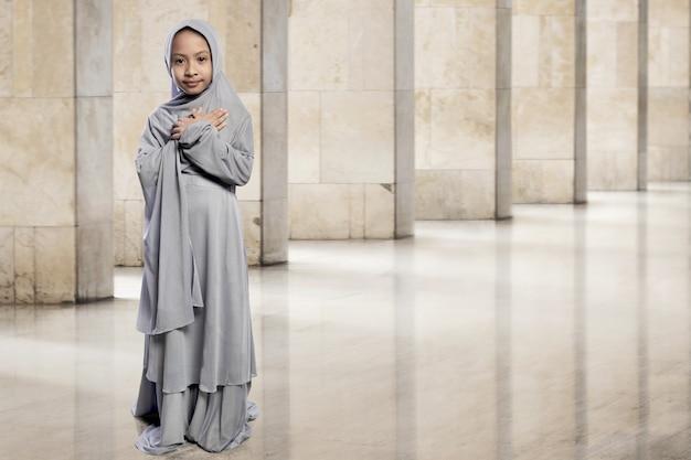 Weinig aziatisch moslimjong geitje in sluier met smileygezicht