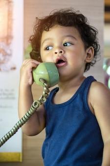 Weinig aziatische babyjongen die op een retro telefoon spreekt.