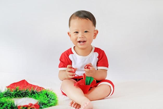 Weinig aziatische babyjongen in kerstmankostuum met de bal van holdingskerstmis decoratief op witte achtergrond. prettige kerstdagen en gelukkig nieuwjaar concept.