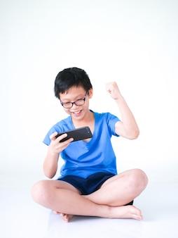 Weinig aziatische jongen die en spel op slimme telefoon witte achtergrond situeert speelt.