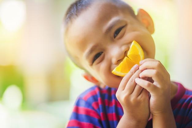 Weinig aziatische jongen gebruikt een plak van sinaasappel voor het glimlachen gezicht