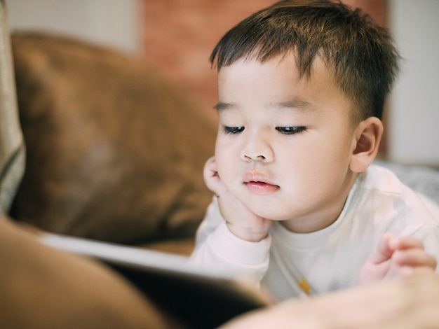 Weinig aziatische jongen het letten op te dichtbij het gebruiken van tablet als gezondheid en technologieconcept